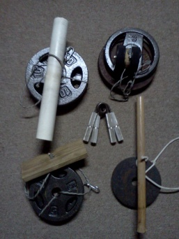 "Grip Training Tools. Clockwise from upper left: Big roller (2"" PVC), Yo-yo roller, Small roller (broomstick), 1"" x 4"" roller. Center: Captains of Crush grippers by Ironmind"